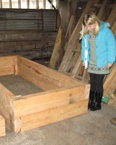 Laura inspects the raised beds in the workshop